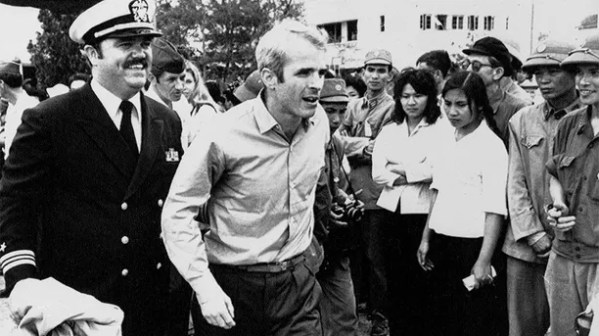 John S. McCain III is escorted by Lt. Cmdr. Jay Coupe Jr., public relations officer, March 14, 1973, to Hanoi's Gia Lam Airport after the POW was released.  (AP Photo/Horst Faas)