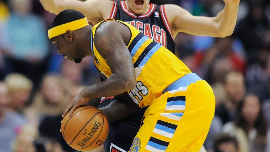 Denver Nuggets guard Ty Lawson, front, runs into Chicago Bulls forward Mike Dunleavy, rear, and is called for a charge in the first quarter of an NBA basketball game on Thursday, Nov. 21, 2013, in Denver. (AP Photo/Chris Schneider)