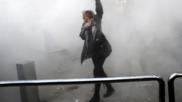 FILE - In this Saturday, Dec. 30, 2017 file photo, taken by an individual not employed by the Associated Press and obtained by the AP outside Iran, a university student attends a protest inside Tehran University while a smoke grenade is thrown by anti-riot Iranian police, in Tehran, Iran. Iran�s top regional foes, Israel and Saudi Arabia, are both watching that country�s protests for signs they could lead to change. Iran�s supreme leader has accused enemies of stoking the unrest. (AP Photo, File)