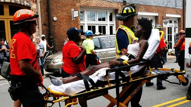"""Rescue workers transport a victim who was injured when a car drove through a group of counter protestors at the """"Unite the Right"""" rally Charlottesville, Virginia, U.S., August 12, 2017.   REUTERS/Joshua Roberts - RTS1BIY2"""
