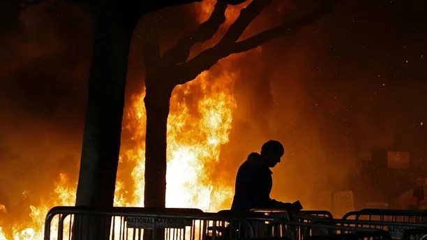 """CORRECTS TO OMIT ANN COULTER- FILE - In this Feb. 1, 2017 file photo, a fire set by demonstrators protesting a scheduled speaking appearance by Breitbart News editor Milo Yiannopoulos burns on Sproul Plaza on the University of California, Berkeley campus. Right-wing showman Milo Yiannopoulos is holding a """"Free Speech Week"""" at the University of California, Berkeley with a planned lineup including conservative firebrands Steve Bannon. The university says it has no confirmation the headline acts will appear but is preparing strong security to head off any more violent protests at the liberal campus. (AP Photo/Ben Margot, File)"""