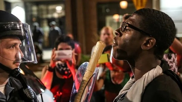 A protester confront police during the second night of demonstrations after a not guilty verdict in the murder trial of former St. Louis police officer Jason Stockley, charged with the 2011 shooting of  Anthony Lamar Smith, who was black, in St. Louis, Missouri, U.S., September 16, 2017.  Photo taken September 16, 2017.  REUTERS/Lawrence Bryant - RC11BAD48DE0