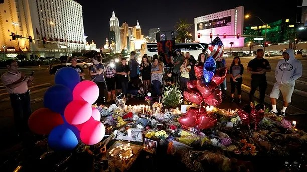 People gather at a makeshift memorial in the middle of Las Vegas Boulevard following the mass shooting in Las Vegas, Nevada, U.S., October 4, 2017. REUTERS/Chris Wattie - RC1229063C00