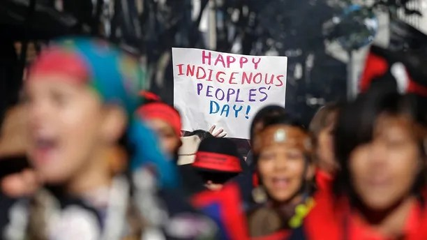 A sign is held aloft during an Indigenous Peoples Day march Monday, Oct. 9, 2017, in Seattle. In 2014, the Seattle City Council voted to stop recognizing Columbus Day and instead turned the second Monday in October into a day of recognition of Native American cultures and peoples. (AP Photo/Elaine Thompson)