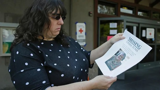 Jessica Tunis stands outside a Red Cross evacuation center and holds a flyer about her missing mother Wednesday, Oct. 11, 2017, in Santa Rosa, Calif. Tunis is searching for her missing mother, Linda Tunis, who was living at a mobile home park when wildfires struck. (AP Photo/Eric Risberg)