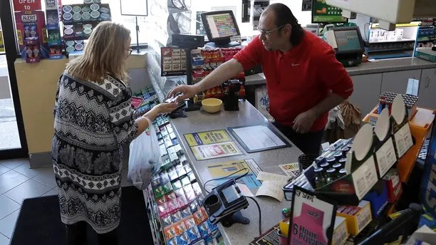 A cashier checks out a customer at a Lukoil service station where the winning ticket for the Mega Millions lottery drawing was sold, Saturday, March 31, 2018, in Riverdale, N.J. (AP Photo/Julio Cortez)