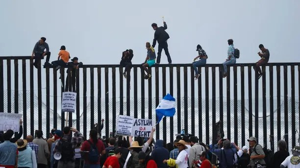 People climb the border wall fence as a caravan of migrants and supporters reached the United States-Mexico border near San Diego, California, U.S., April 29, 2018.    REUTERS/Mike Blake - HP1EE4T1D57HL