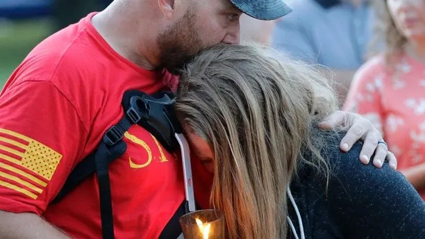 Santa Fe High School freshman Kylie Trochesset, right, is comforted by her father, Jared, during a prayer vigil following a shooting at Santa Fe High School in Santa Fe, Texas, on Friday, May 18, 2018. (AP Photo/David J. Phillip)
