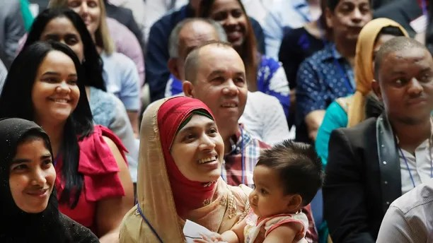 Mosammat Rasheda Akter, center, of Bangladesh, holds her seven-month-old daughter Fahmida during a naturalization ceremony, Tuesday, July 3, 2018, at the New York Public Library's Celeste Bartos Forum. Two hundred people from 50 countries gained citizenship. (AP Photo/Mark Lennihan)