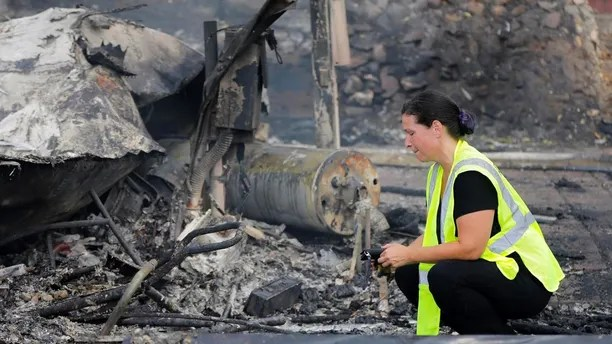 A woman looks at the charred remains of her mobile home after it was destroyed by a wildfire in the Alpine Oaks Estates where she has lived for more than eight years, in Alpine, Calif., Saturday, July 7, 2018. (Howard Lipin/The San Diego Union-Tribune via AP)