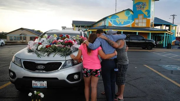 People pray by a car thought to belong to a victim of Thursday's boating accident before a candlelight vigil in the parking lot of Ride the Ducks Friday, July 20, 2018, in Branson, Mo. One of the company's duck boats capsized Thursday night resulting in over a dozen deaths on Table Rock Lake. (AP Photo/Charlie Riedel)