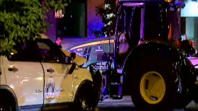 Two police officers were injured in a slow chase with a John Deere tractor in downtown Denver Friday night, police said.