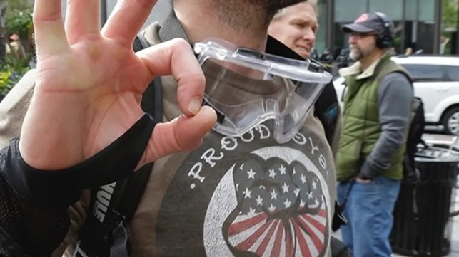 A man, seen in this file photo, is wearing a shirt supporting the Proud Boys conservative group and makes a hand sign as he takes part in a May Day protest, Monday, May 1, 2017, in Seattle.
