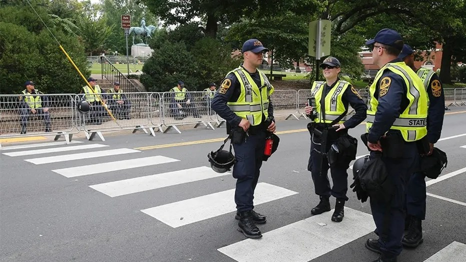 State Police on Saturday patrol the road in front of Market Street park as they lock down the downtown area in anticipation of the anniversary of last year's Unite the Right rally in Charlottesville, Va.