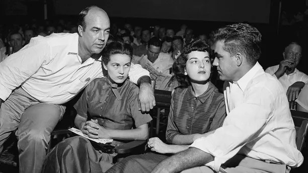 """FILE - In this Sept. 23, 1955, file photo, J.W. Milam, left, his wife, second left, Roy Bryant, far right, and his wife, Carolyn Bryant, sit together in a courtroom in Sumner, Miss. Bryant and his half-brother Milam were charged with murder but acquitted in the kidnap-torture slaying of 14-year-old black teen Emmett Till in 1955 after he allegedly whistled at Carolyn Bryant. The men later confessed in a magazine interview but weren't retried; both are now dead. Citing """"new information,"""" the U.S. Justice Department has reopened the investigation into Till's death. (AP Photo, File)"""