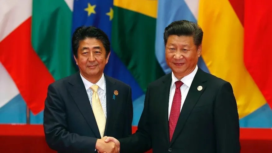 """FILE- In this Sunday, Sept. 4, 2016, file photo, Japan's Prime Minister Shinzo Abe, left, poses with China's President Xi Jinping for a photo before a group photo session for the G20 Summit in Hangzhou in eastern China's Zhejiang province. Four years after they went into a nosedive, tense relations between China and Japan may finally be headed for a sustained return to some semblance of normalcy. Those hopes rest largely on a statement by Chinese President Xi Jinping at a meeting Monday with Japanese Prime Minister Shinzo Abe that it was time to """"put aside disruptions"""" and bring ties """"back on the normal track."""" (AP Photo/Ng Han Guan, File)"""