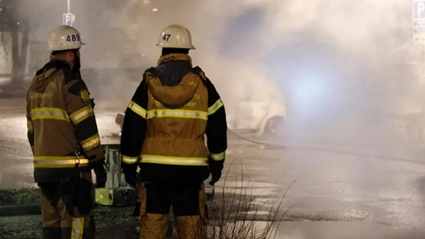 Firefighters survey the scene in the suburb of Rinkeby where riots erupted on Monday night.