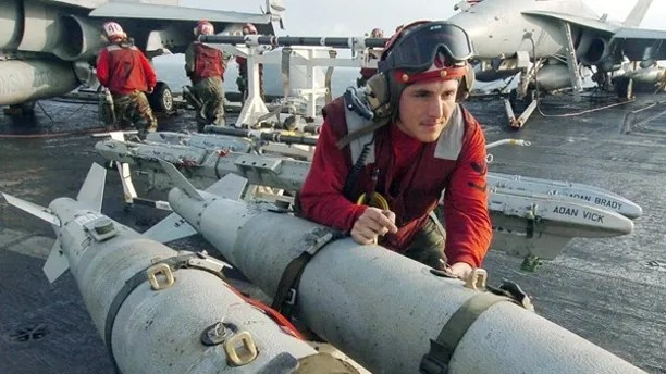"""U.S. Aviation Ordnanceman 3rd Class Joshua Silva, assigned to """"Gunslingers"""" of Strike Fighter Squadron One Zero Five (VFA-105), helps push a weapons skid loaded with three GBU-38 500 pound satellite guided bombs on the flight deck aboard USS Harry S. Truman (CVN 75), in the Gulf south of Iraq, in this handout photograph released on December 15, 2004. The aircraft from Carrier Air Wing Three (CVW-3) embarked aboard Truman are providing close air support and conducting intelligence, surveillance, and reconnaissance missions in ongoing military operations over Iraq. REUTERS/HO/US Navy/Mate Airman Ryan O'Connor  HH/ABP - RTRIDJQ"""