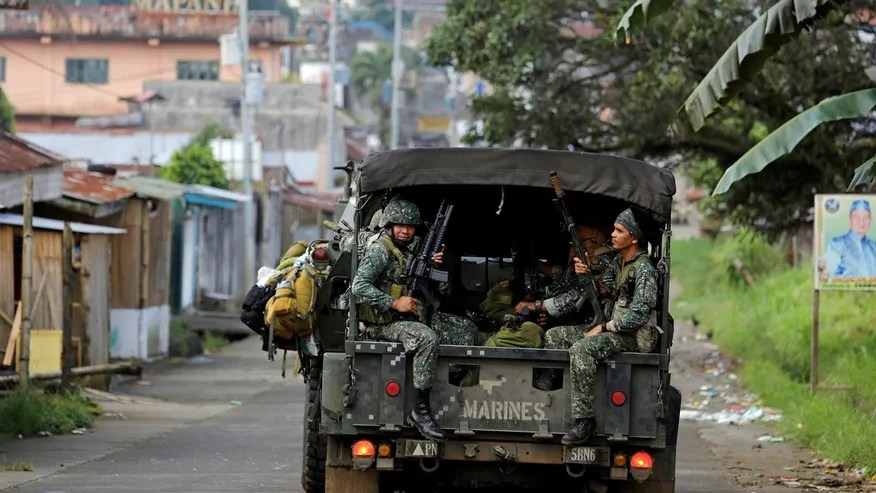 Philippine Marines ride in a military vehicle as they advance their position against ISIS-linked militants in Marawi City, southern Philippines May 30, 2017.