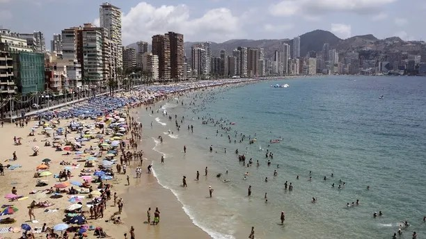 People relax at the beach during a hot summer day in Benidorm, Spain, July 26, 2015. Spain hosted record numbers of tourists in the first half of 2015, feeding an economic rebound as sun-seekers from Europe and the United States headed for its shores. Spain got 29.2 million foreign visitors in the six months to June, up 4.1 percent from the same period a year ago, according to Frontur, an industry ministry body.  REUTERS/Heino Kalis - RTX1LV7B