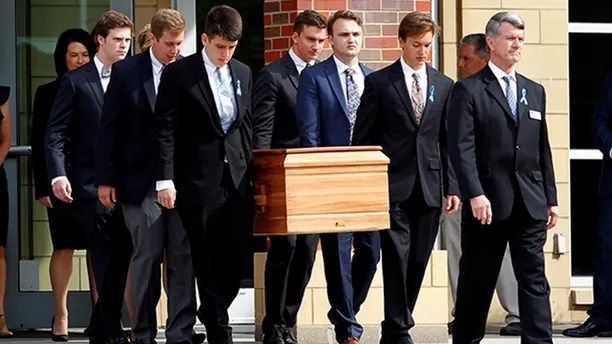 The casket of Otto Warmbier is carried to the hearse followed by his family and friends after a funeral service for Warmbier, who died after his release from North Korea, at Wyoming High School in Wyoming, Ohio, U.S. June 22, 2017.  REUTERS/John Sommers II - RTS187RK