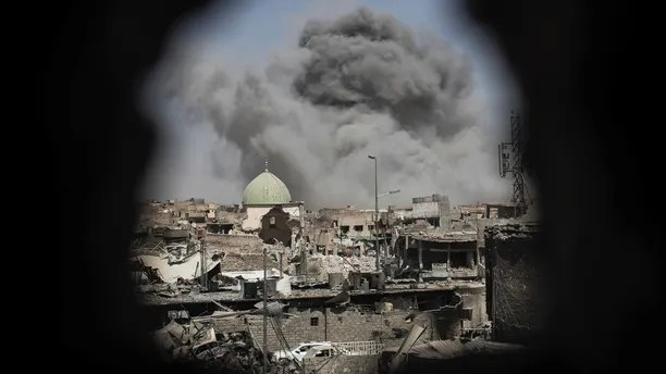 A bomb explodes behind the al-Nuri mosque complex, as seen through a hole in the wall of a house, as Iraqi Special Forces move toward Islamic State militant positions in the Old City of Mosul, Iraq, Thursday, June 29, 2017. (AP Photo/Felipe Dana)