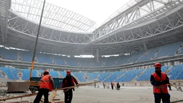 Labourers work at a new stadium under construction on Krestovsky Island, known as Zenit Arena, that will host 2017 FIFA Confederations Cup and 2018 FIFA World Cup matches, in St. Petersburg, Russia, October 3, 2016. REUTERS/Pawel Kopczynski - RTSQK9H