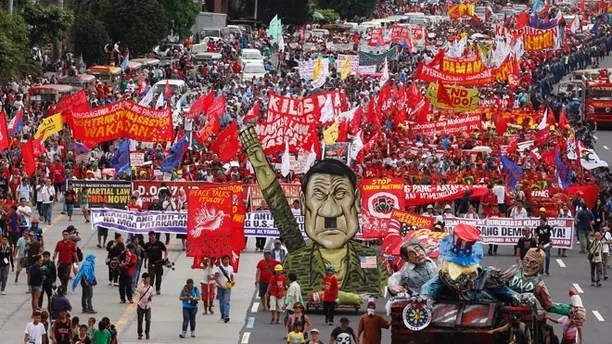 Thousands of protesters march towards the Lower House with an effigy of President Rodrigo Duterte, lower right, to demand that he deliver on a wide range of promises he made in his first state of the nation address last year, from pressing peace talks with Marxist guerrillas, which is currently on hold, to upholding human rights and the rule of law Monday, July 24, 2017 at suburban Quezon city northeast of Manila, Philippines. It was the first time that the leftists protesters have displayed an effigy of Duterte. (AP Photo/Bullit Marquez)