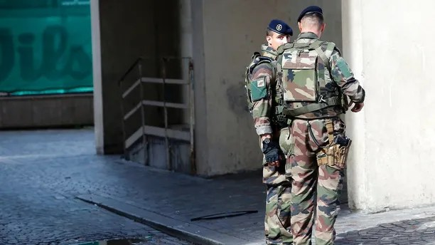 French soldiers stand near the scene where French soldiers were hit and injured by a vehicle in the western Paris suburb of Levallois-Perret near Paris, France, Wednesday, Aug. 9, 2017. French police are searching for a driver who slammed his BMW into a group of soldiers, injuring six of them in an apparent ambush before speeding away, officials said. The incident in Levallois, northwest of Paris, is the latest of several attacks targeting security forces in France.(AP Photo/Kamil Zihnioglu)