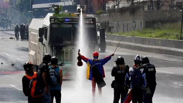 A demonstrator stands in front of a riot security forces vehicle during a rally against President Nicolas Maduro in Caracas, Venezuela, May 24, 2017. REUTERS/Carlos Garcia Rawlins - RTX37GUR