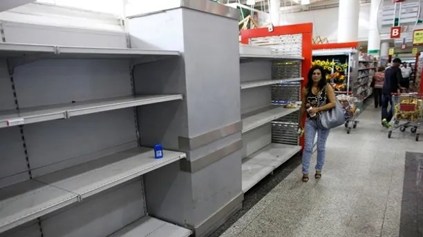 """A woman walks past an empty section where toilet paper should be on display in a super market in Caracas May 17, 2013. Supplies of food and other basic products have been patchy in recent months, with long queues forming at supermarkets and rushes occurring when there is news of a new stock arrival. The situation has spawned jokes among Venezuelans, particularly over the lack of toilet paper. The government announced this week it was importing 50 million rolls to compensate for """"over-demand due to nervous buying"""". REUTERS/Jorge Silva (VENEZUELA - Tags: POLITICS BUSINESS SOCIETY) - RTXZQYE"""