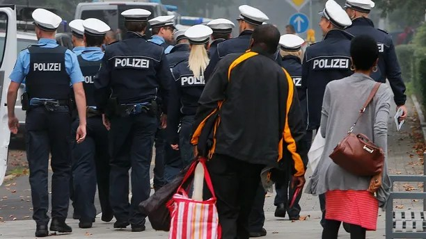 A couple has left its apartment and walk behind police during an evacuation of more than 60 000 people in Frankfurt, Germany, Sunday, Sept. 3, 2017. The evacuation became necessary due to an unexploded 1.8 ton WW II bomb that will be diffused later in the day. (AP Photo/Michael Probst)