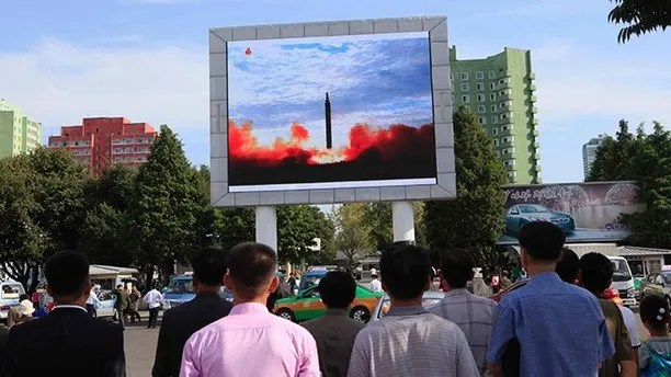 """People watch a launching of a Hwasong-12 strategic ballistic rocket aired on a public TV screen at the Pyongyang Train Station in Pyongyang, North Korea, Saturday, Sept. 16, 2017. North Korean leader Kim Jong Un said his country is nearing its goal of """"equilibrium"""" in military force with the United States, as the United Nations Security Council strongly condemned the North's """"highly provocative"""" ballistic missile launch over Japan on Friday. (AP Photo/Jon Chol Jin)"""