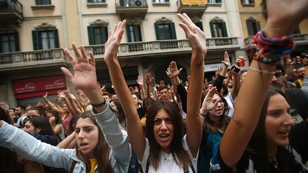 Protestors shout as they gather in front of the Spanish police station in downtown Barcelona, Spain, Tuesday Oct. 3, 2017. Labor unions and grassroots pro-independence groups are urging workers to hold partial or full-day strikes and demonstrations throughout Catalonia to protest alleged brutality by police during a referendum on the region's secession from Spain that left hundreds of people injured. (AP Photo/Francisco Seco)