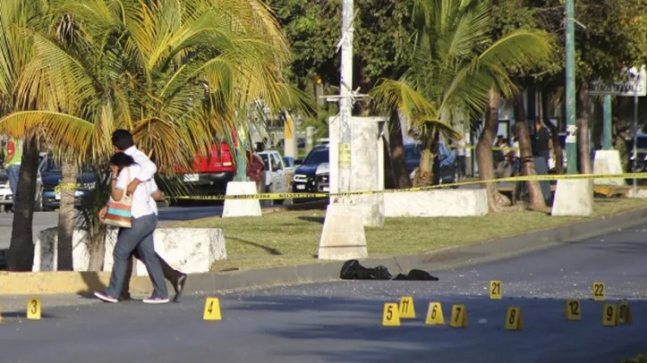 A couple walks past bullet casings at a crime scene in Cancun in January 2017.