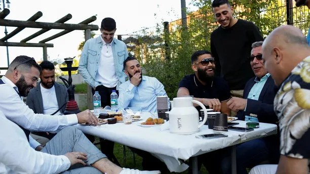 """Guests from places within Denmark and Northern Europe sit together at the engagement party of a resident in Mjolnerparken, a housing estate that features on the Danish government's """"Ghetto List"""", in Copenhagen, Denmark, May 6, 2018. REUTERS/Andrew Kelly SEARCH """"DENMARK GHETTO"""" FOR THIS STORY. SEARCH """"WIDER IMAGE"""" FOR ALL STORIES. THE IMAGES SHOULD ONLY BE USED TOGETHER WITH THE STORY - NO STAND-ALONE USES. TPX IMAGES OF THE DAY - RC11F9055400"""