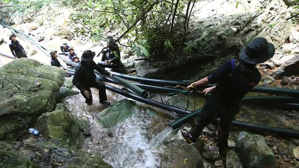 Thai soldiers drag water pipes that will help bypass water from entering a cave where 12 boys and their soccer coach have been trapped since June 23, in Mae Sai, Chiang Rai province, in northern Thailand Saturday, July 7, 2018. Thai authorities are racing to pump out water from the flooded cave before more rains are forecast to hit the northern region. (AP Photo/Sakchai Lalit) (AP Photo/Sakchai Lalit)