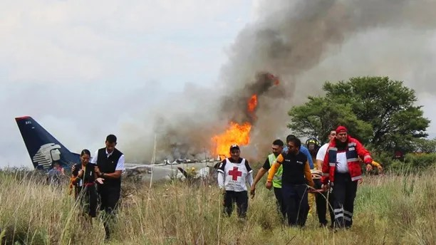"""Rescue workers and firefighters are seen at the site where an Aeromexico airliner has suffered an """"accident"""" in a field near the airport of Durango, Mexico, Tuesday, July 31, 2018. (Civil Defense Office of Durango Photo via AP)"""