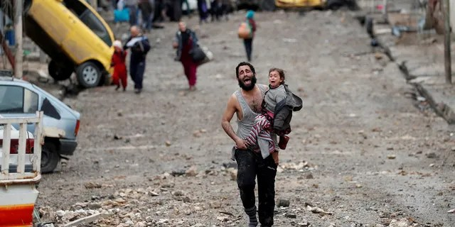 A man cries as he carries his daughter from an ISIS-controlled area of Mosul, Iraq