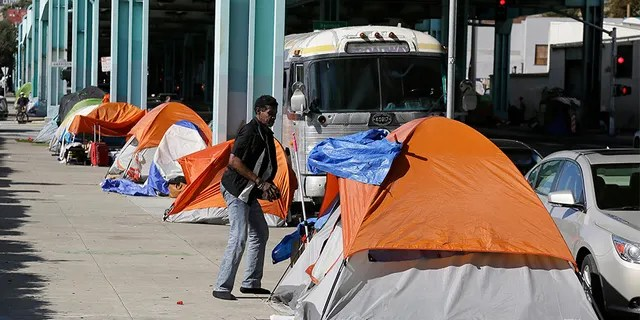 A man stands outside his tent on Division Street in San Francisco.
