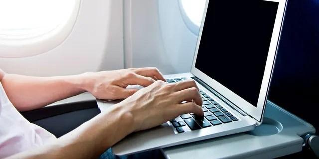 Man using laptop computer on airplane. (Boana)