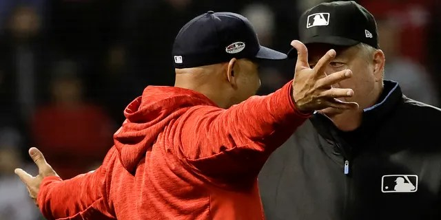 Boston Red Sox manager Alex Cora argues a strike three call with umpire Joe West during the fifth inning in Game 1 of a baseball American League Championship Series against the Houston Astros on Saturday, Oct. 13, 2018, in Boston.