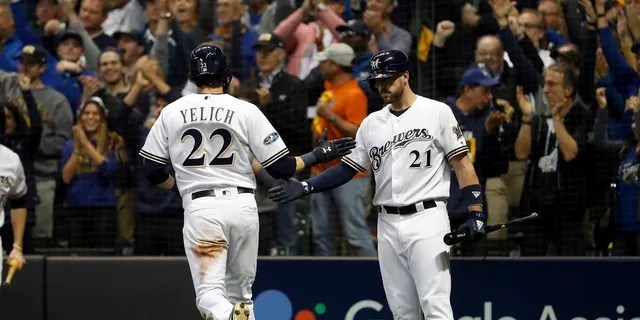File - Milwaukee Brewers' Christian Yelich (22) celebrates with Travis Shaw (21) after scoring a run during the second inning of Game 6 of the National League Championship Series baseball game against the Los Angeles Dodgers Friday.