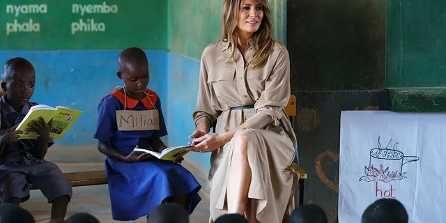 First lady Melania Trump helps a student as she visits a language class at Chipala Primary School, in Lilongwe, Malawi, Thursday, Oct. 4