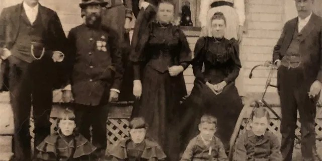 Maker would often write home to his family during World War I. He is pictured here as a young boy, on the far right of the bottom row. To his side, from right to left, are his stepsister Harriet, sister Eva and brother Clifford (Kip). His uncle Edward, wearing a Union Army uniform,is second from the left in the middle row, next to Edward's brother, Andrew. Both of those men fought for 19th Maine Regiment during the Civil War. Maker's father, Winfield, is standing in front of the bicycle on the far right.