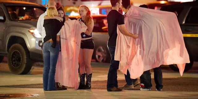 People comfort each other as they stand near the scene of a mass shooting in Thousand Oaks, Calif., early Thursday morning.