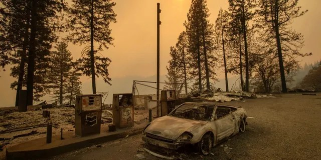 As the Camp Fire burns nearby, a scorched car rests by gas pumps near Pulga, Calif., on Sunday.