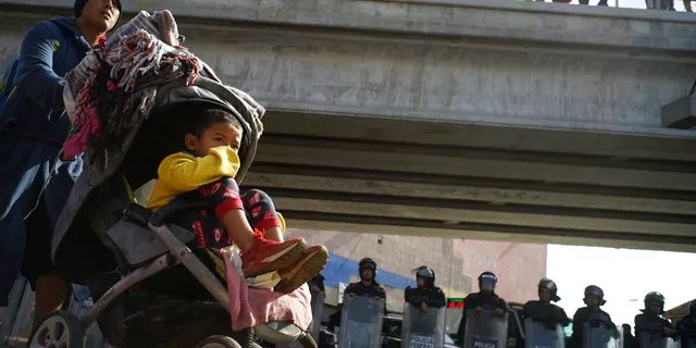 A migrant man pushes a child in a baby stroller past a cordon of riot police as he joins a small group of migrants trying to cross the border together at the Chaparral border crossing in Tijuana, Mexico, Thursday, Nov. 22, 2018. A small group of Central American migrants marched peacefully to a border crossing in Tijuana Thursday to demand better conditions and push to enter the U.S. (AP Photo/Ramon Espinosa)