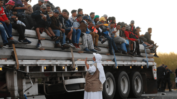"""A Catholic nun gives travel advice to Central American migrants riding in the bed of a semi-trailer, as they move toward the U.S. border, in Ixtlán del Rio, Nayarit, Mexico, Tuesday, Nov. 13, 2018. The U.S. government said it was starting work Tuesday to """"harden"""" the border crossing from Tijuana, Mexico, to prepare for the arrival of a migrant caravan leapfrogging its way across western Mexico. (AP Photo/Marco Ugarte)"""