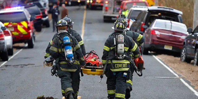 Firefighters carry a stretcher to the scene of a fatal fire at in Colts Neck, New Jersey, on Nov. 20, 2018.